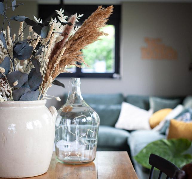 Salon, canapé vert, vase, dame jeanne, fleurs sechées, décoration d'intérieur Neuchâtel, presation décoration d'intérieur.